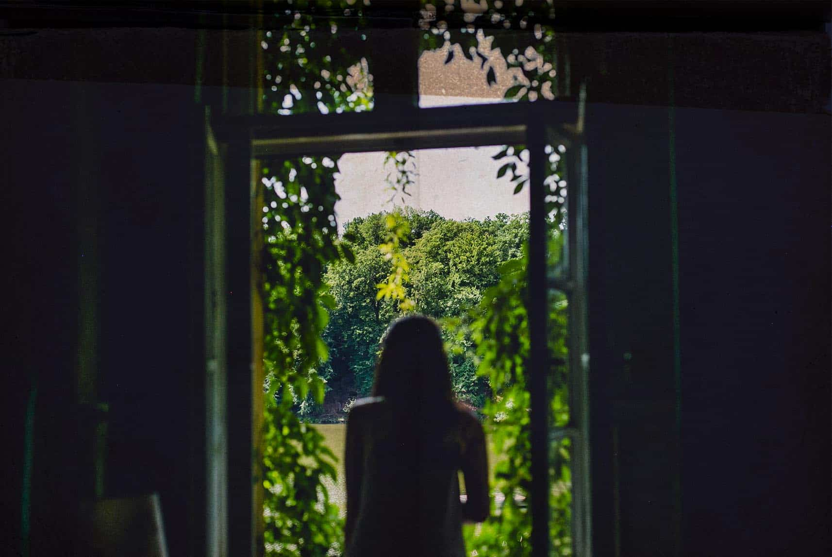 bride staring at a beautiful sight through a window