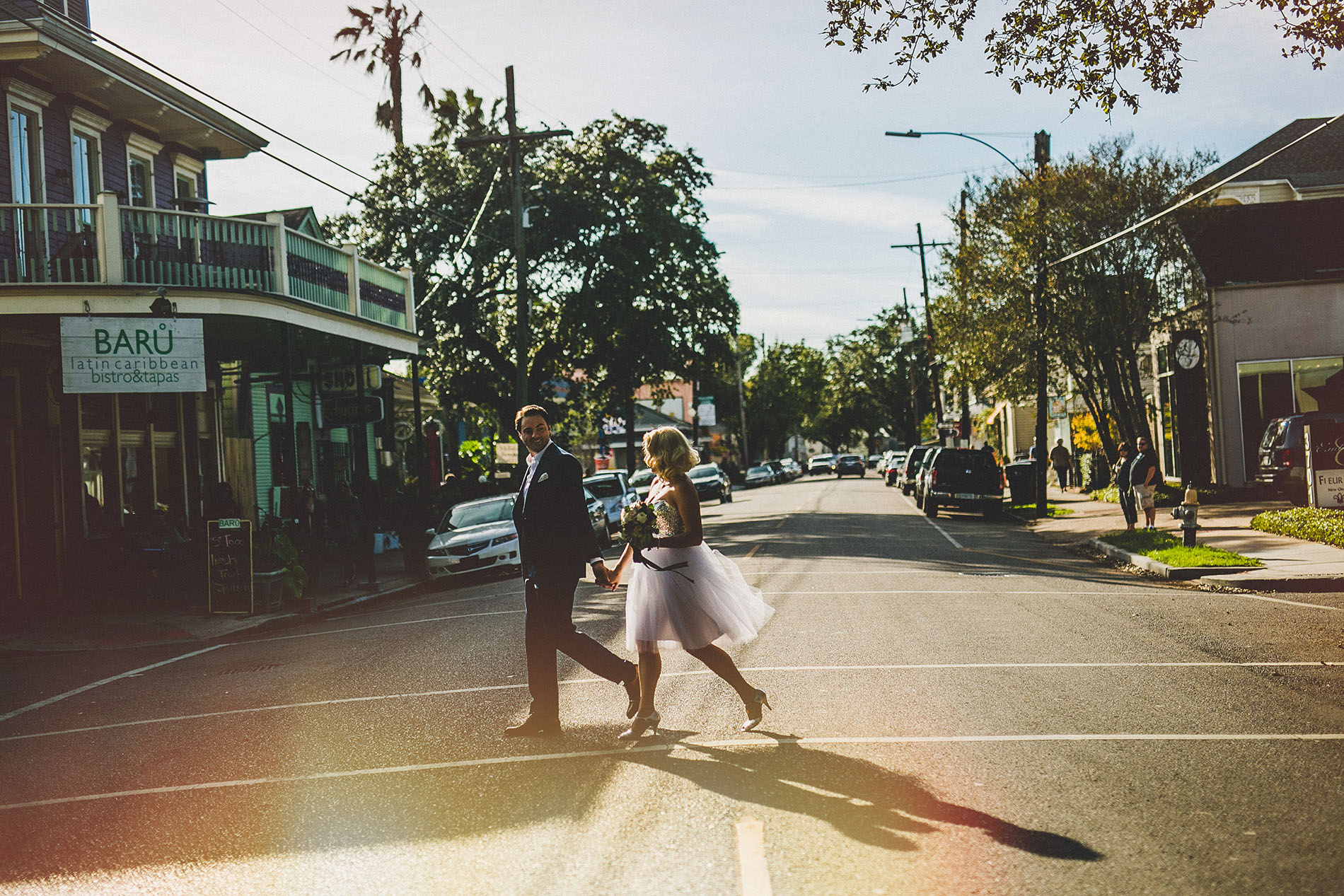 bride and groom walking of the street of new orleans for the photo shoot