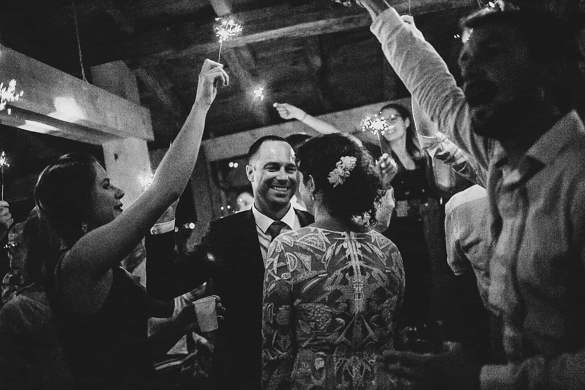 people dancing with sparkles surrounding bride and groom