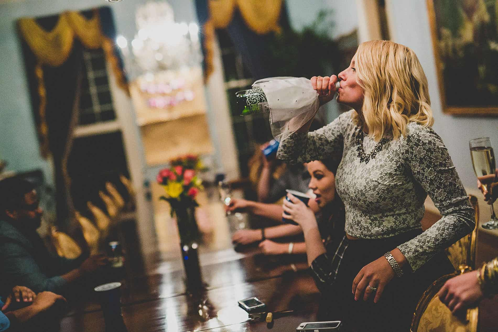 sexy bride drinking champagne from the bottle
